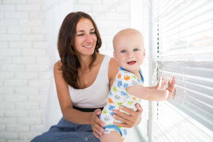 Kleiner niedlicher fröhlicher Junge mit einer glücklichen fürsorgliche Mutter