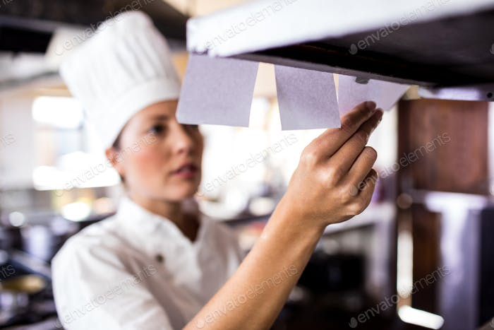 Female chef looking at order list in kitchen at hotel