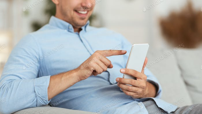 Closeup of smiling guy using smartphone at home