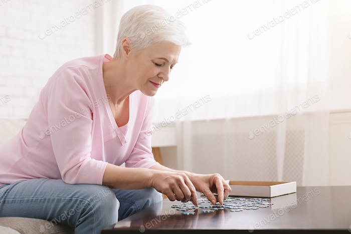 Senior lady playing jigsaw puzzle at home, empty space