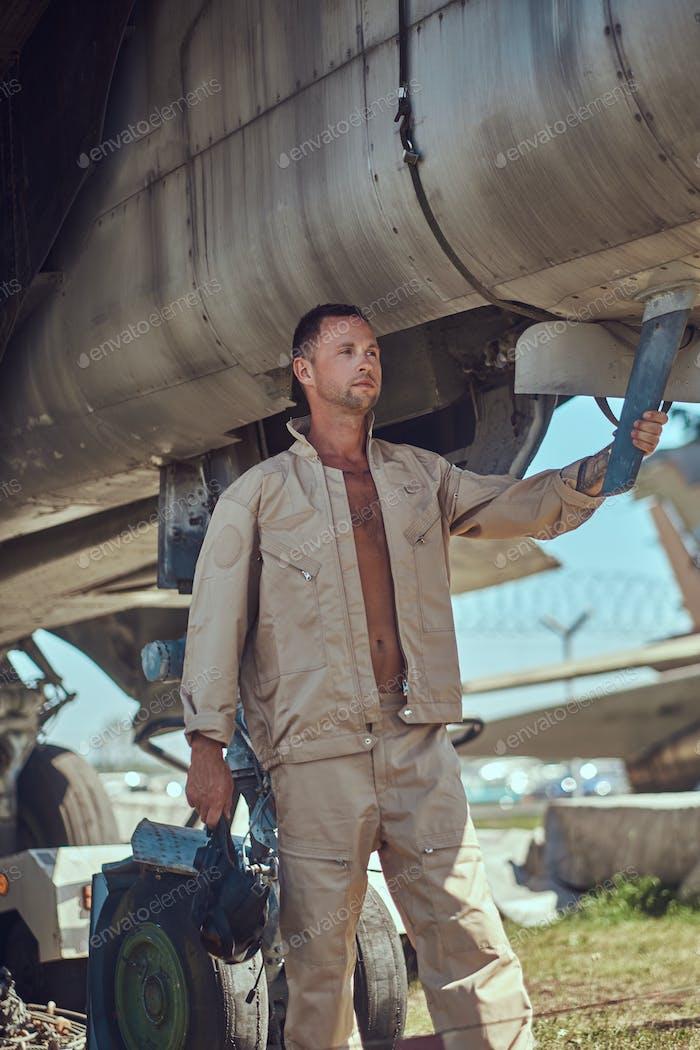 Mechanic in uniform standing near a war fighter-interceptor in an open-air museum.