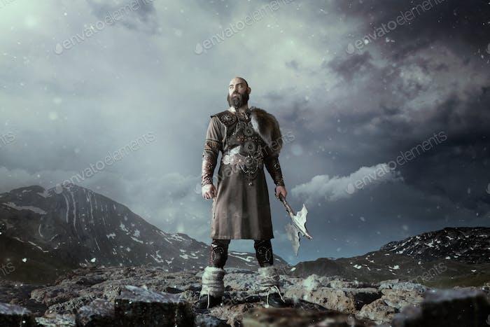 Wikinger mit Axt stehend in felsigen Bergen