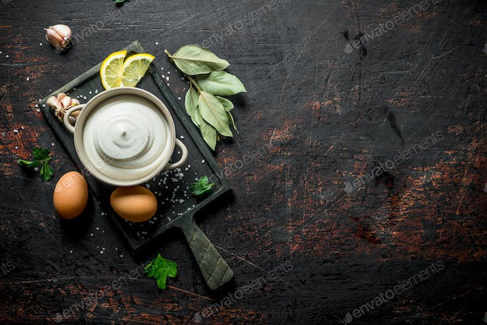 Mayonnaise in bowl on cutting Board with lemon slices, eggs and Bay leaf.