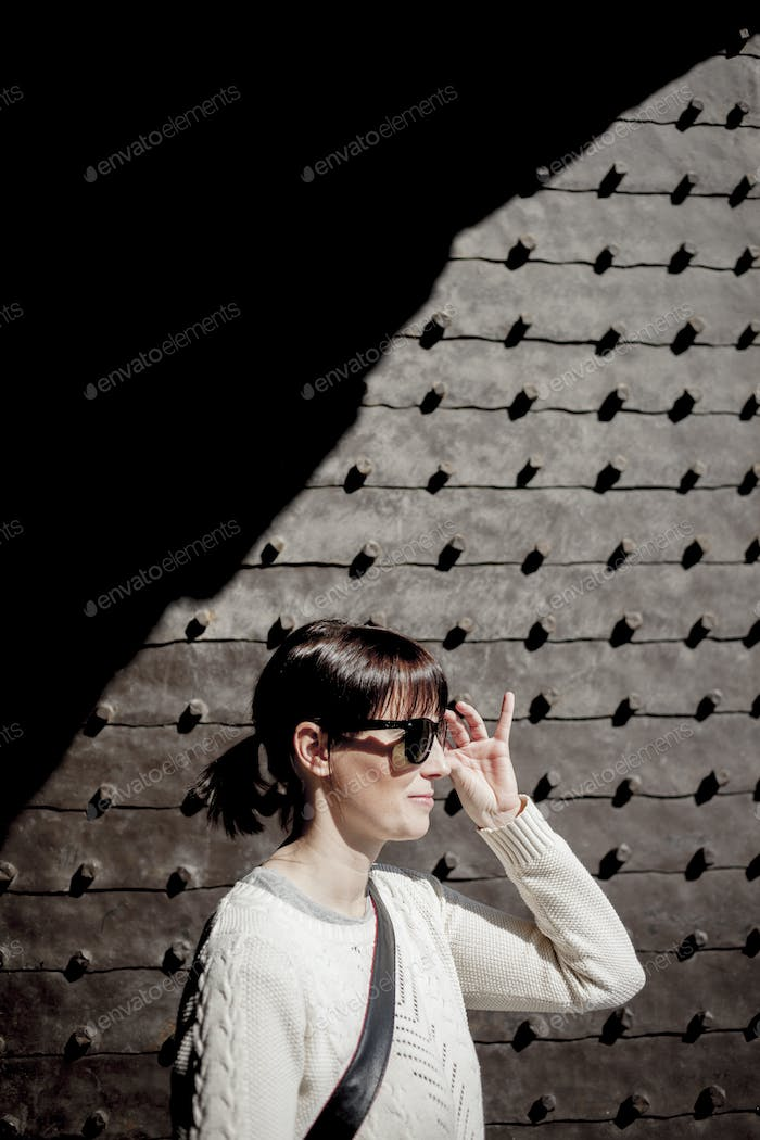 Mid adult woman wearing sunglasses against wall