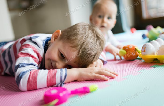 Cute little children playing while sitting on carpet