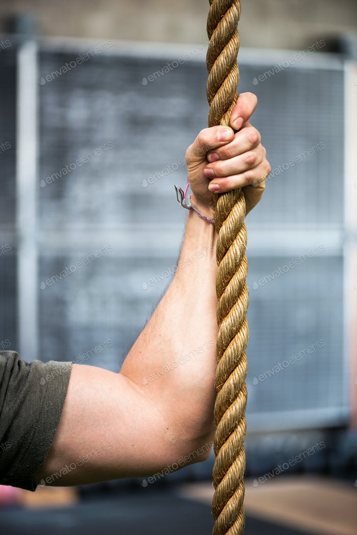 Strong muscular male arm holding a rope