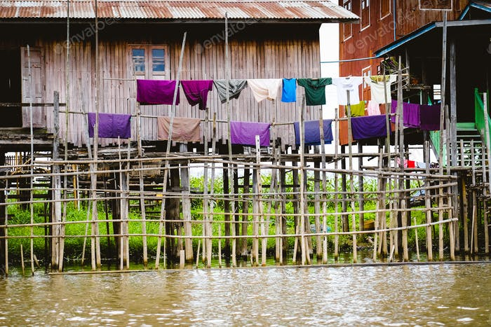 Traditional wooden houses on Inle lake with drying colorful clothes