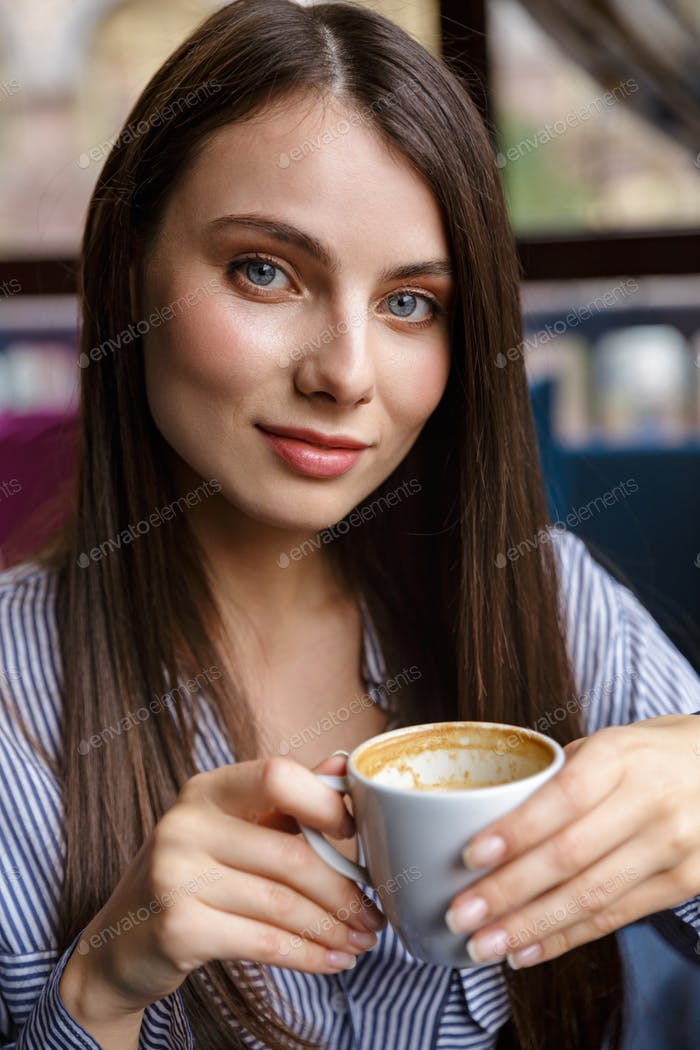 Beautiful young brunette woman drinking coffee