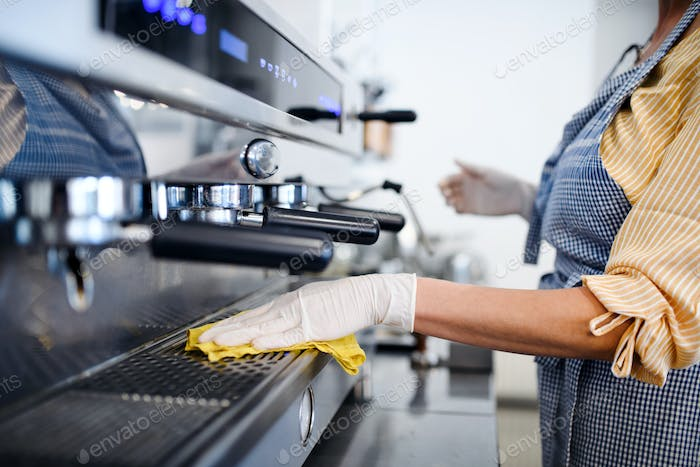 Coffee shop woman owner working with gloves , disinfecting machine