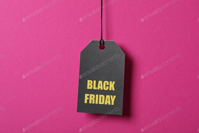 Inscription Black Friday on price tag on pink background, copy space