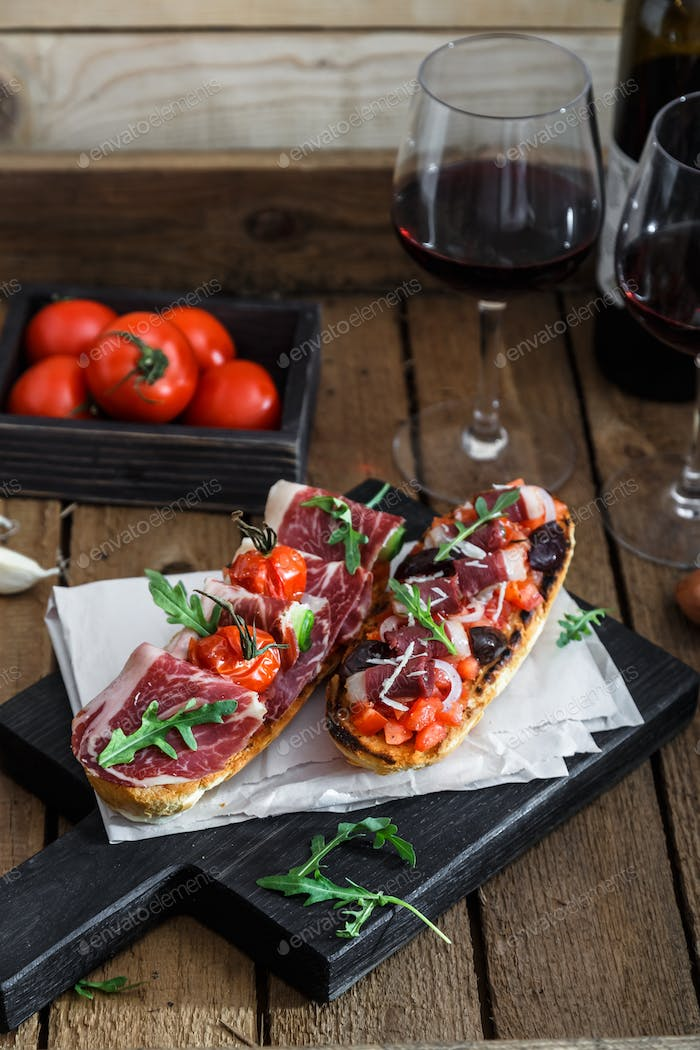Spanish tapas with slices jamon serrano, salami, olives and cheese cubes on a wooden table.