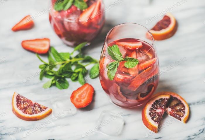 Frucht-erfrischende Sangria Cocktails mit Eis und Minze, Marmorhintergrund