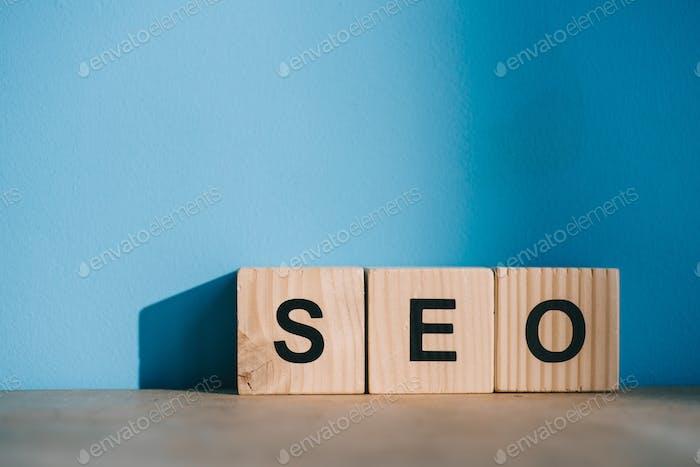alphabet blocks with SEO word on blue background