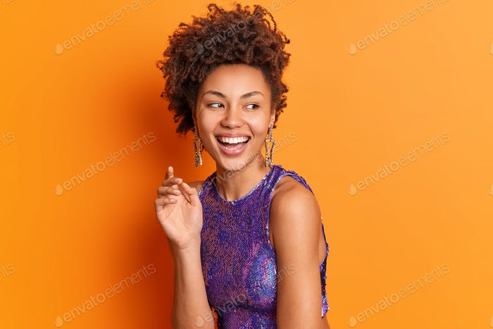 Fashion portrait of happy stylish African American woman in bright clothes earrings smiles broadly l