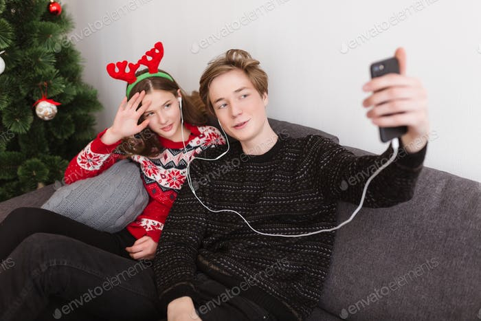 Beautiful teen couple sitting on sofa at home in earphones and taking selfie spending time together