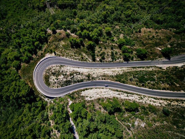 Aerial view of curve road with a car on the mountain with green forest in Croatia