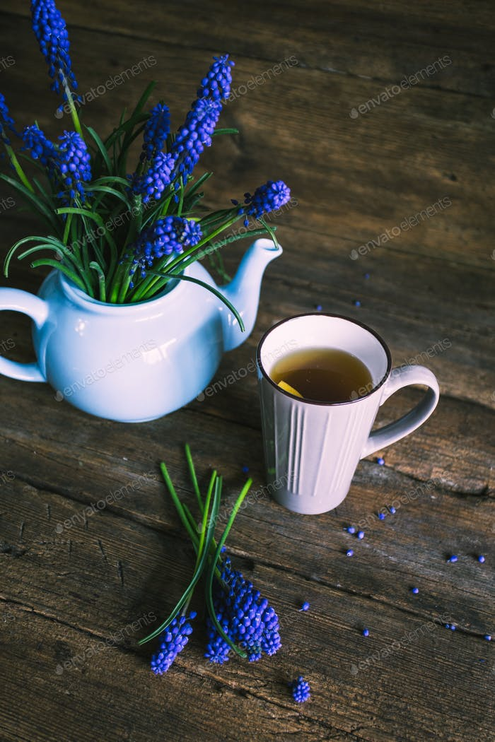 Blue flowers in a teapot with a cup of tea on wooden background.