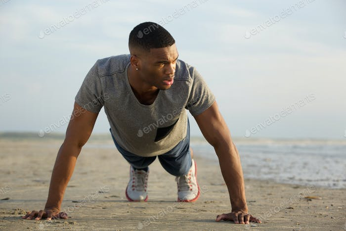 Young guy doing push ups at the beach