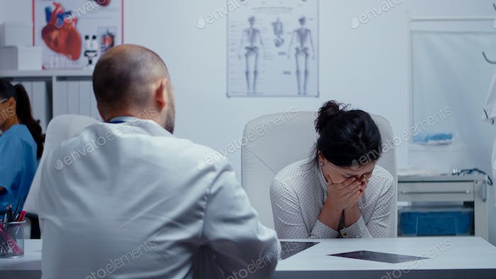 Woman crying at doctor after bad news