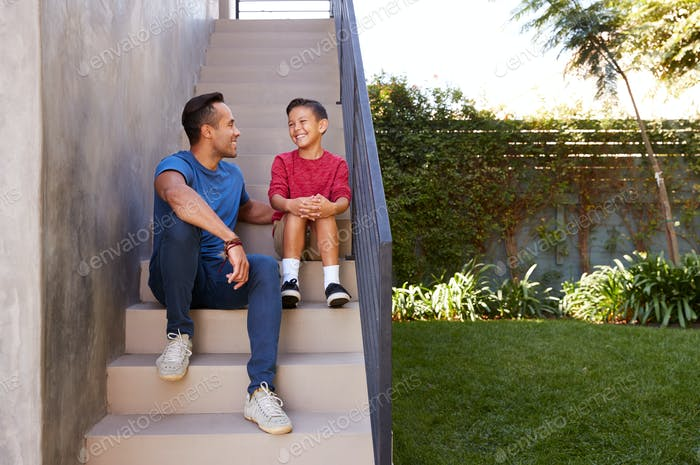 Smiling Hispanic Father And Son Sitting On Steps In Garden Talking Together