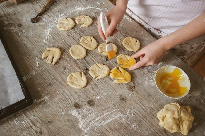 female woman artisan baker at home baking a sweet dough cookies