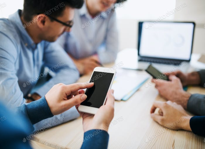 Group of young businesspeople with smartphone having meeting in office. Copy space.