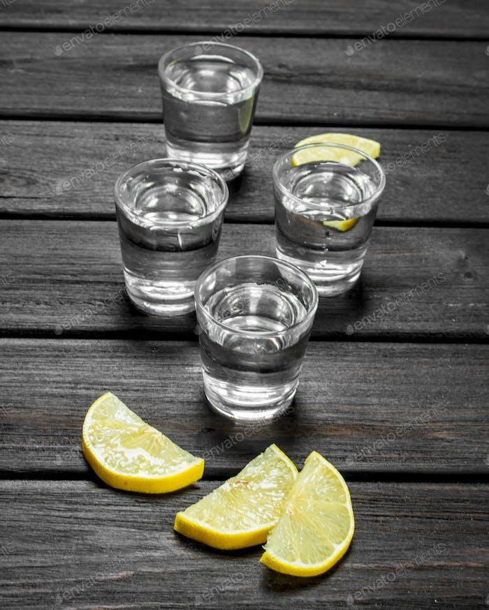 Vodka in a shot glass and lemon slices.