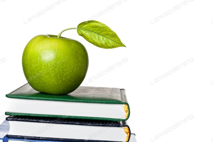 Green apple on textbook isolated