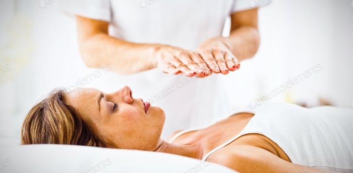 Young woman receiving reiki treatment