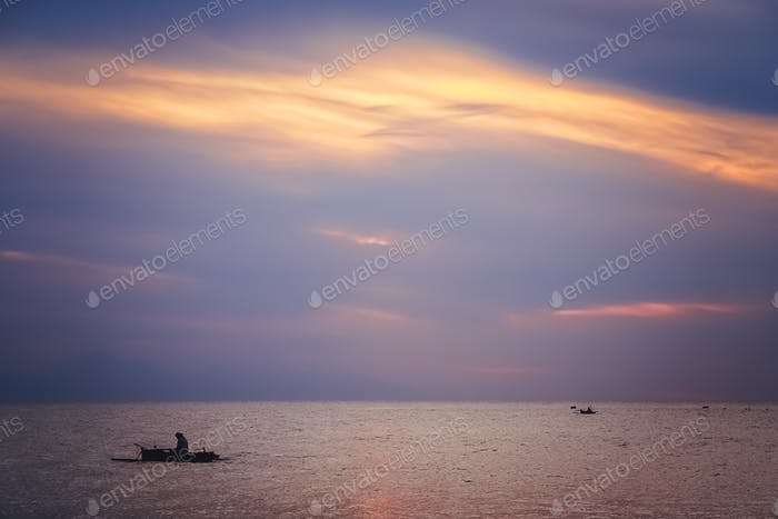 Small fisherman boat sailing at dusk