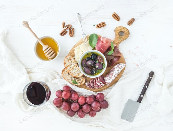 Wine appetizer set. Glass of red, grapes, parmesan cheese, meat variety, bread slices