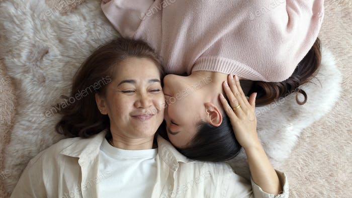 Attractive beautiful cheerful authentic real family two people laying down look at camera