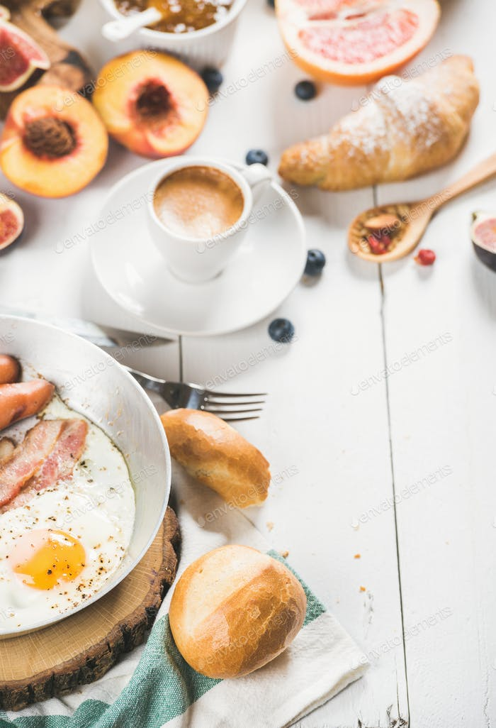 Fried egg with sausages and bacon, bread, croissants, coffee