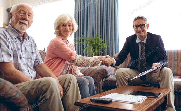 Portrait of matured Caucasian male physician shaking hand and smiling at retirement home