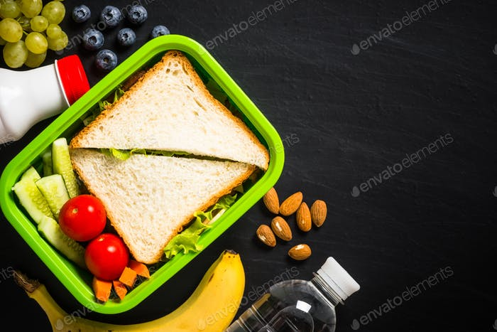 Lunch box with sandwich and fruits on black