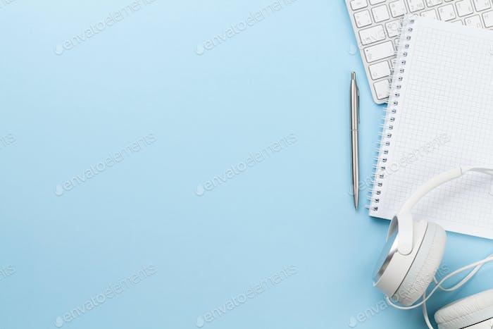 Schreibtisch mit Zubehör, Kopfhörern und leerem Notizblock