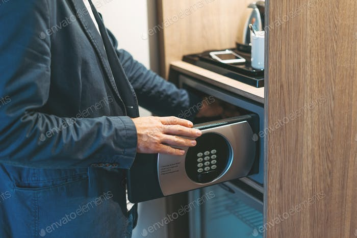 Adult man in blue jacket uses safe in the hotel room