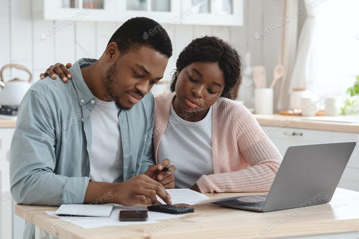 Portraif Of Young African Couple Sitting At Table In Kitchen, Reading Documents