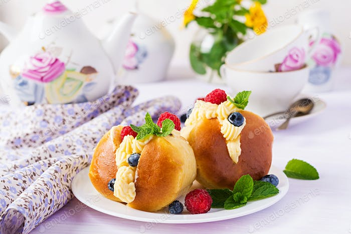 Rum baba decorated with whipped cream and fresh raspberry, blueb
