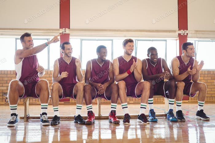 Excited basketball player sitting on bench