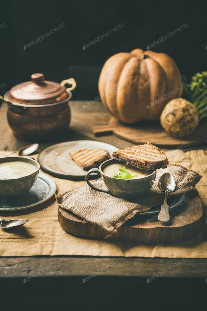Celery cream soup and toast, fresh pumpkin at background