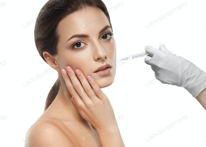 Plastic surgery beauty concept - beautiful young woman face hand in glove syringe making injection