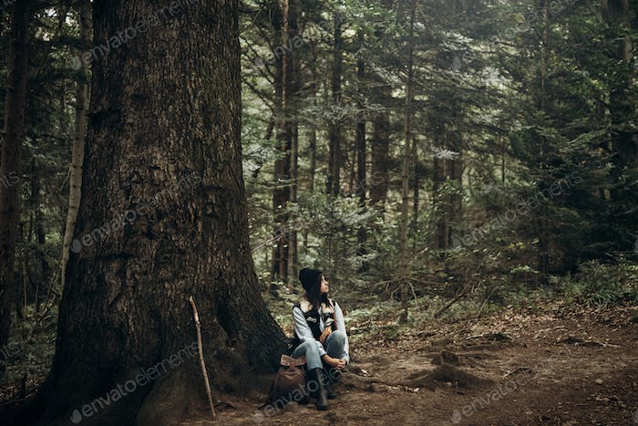 hipster traveler with backpack sitting under tree in woods