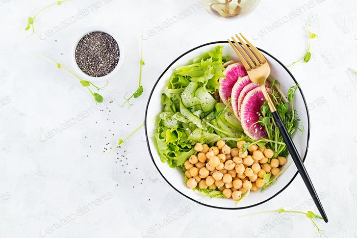 Vegan Buddha bowl with chickpeas, watermelon radish, cucumber and peas sprouts
