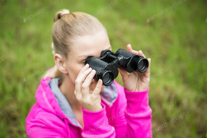 Upward view of a female hiker looking through the binoculars