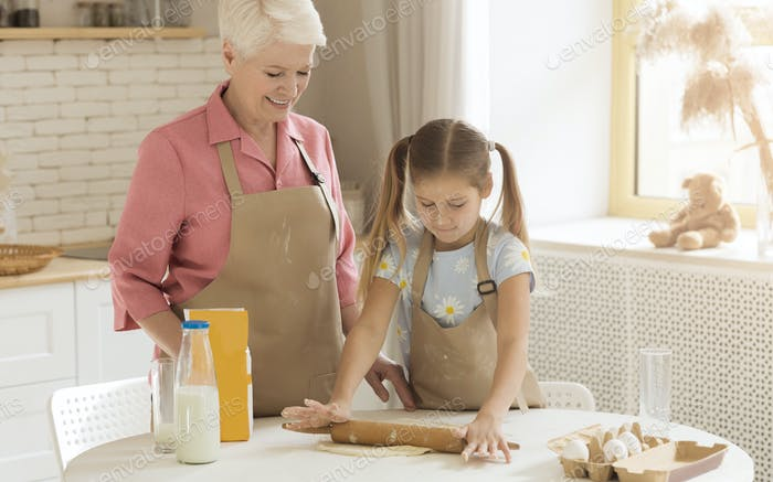 Adorable child learning how to bake from her granny at home