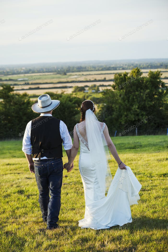 Rear view of bride and groom walking hand in hand across a grassy slope, with a view over the