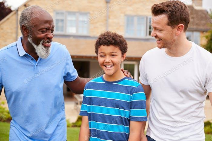 Vater mit Sohn und Großvater von Multi-Generation Mixed Race Familie Walking In Garten Zu Hause