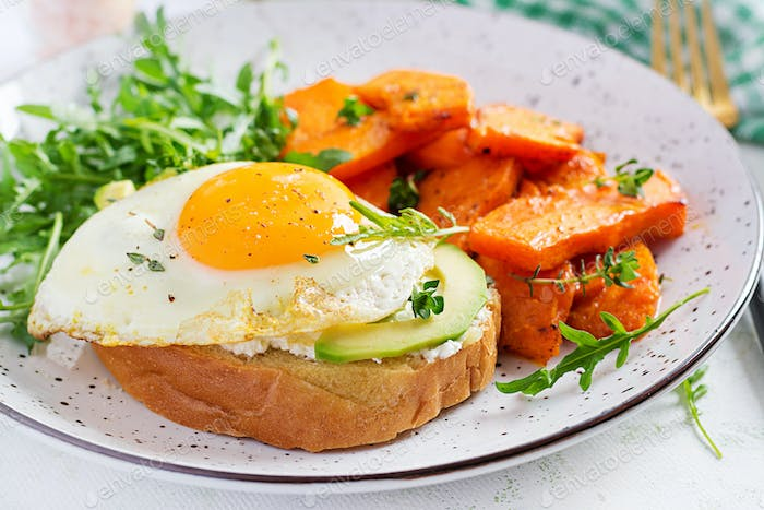 Avocado sandwich with fried egg and fried sliced pumpkin