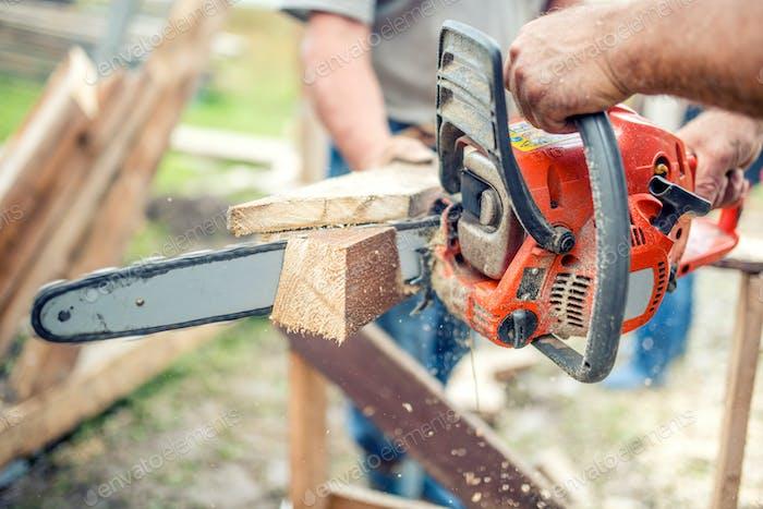 Industriearbeiter schneiden Holz mit Kettensäge. Männer Sägen mit elektrischen Kettensäge